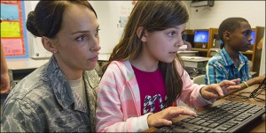 Amy Perry, left, watches as her daughter, Kayla Perry, works at the Operation LINK afterschool program held this spring in Goldsboro. Amy Perry is a technical sergeant in the U.S. Air Force, where she inspects aircraft for defects at Seymour Johnson Air Force Base.