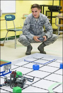 USAF airman first class Eagan Nadeau pilots one of the student robots.