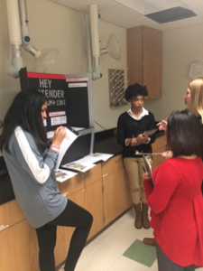 Pitt County high school students Shinjini Misra and Kyra Miles receive feedback on their project from ECU student judges.