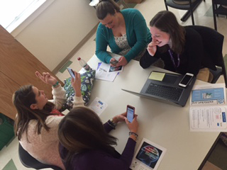 BS Mathematics Education students (clockwise from far left) Megan Taylor, Carson Gombatz, Sarah Marsh, and Kaylin Carlton look for an assessment app on their phone during one conference breakout session.