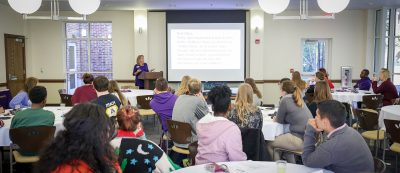 Members of the ECU College of Education Scholars, Education Living-Learning Community students, and other Teacher Education students listen to Lisa Godwin speak about being a first year teacher.