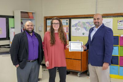 Dr. Leonard Annetta, right, and Shawn Moore, left, presents eighth-grade C.M. Eppes Middle School teacher Allie Smith with the inaugural John C. Park Scholarship Thursday, March 8.