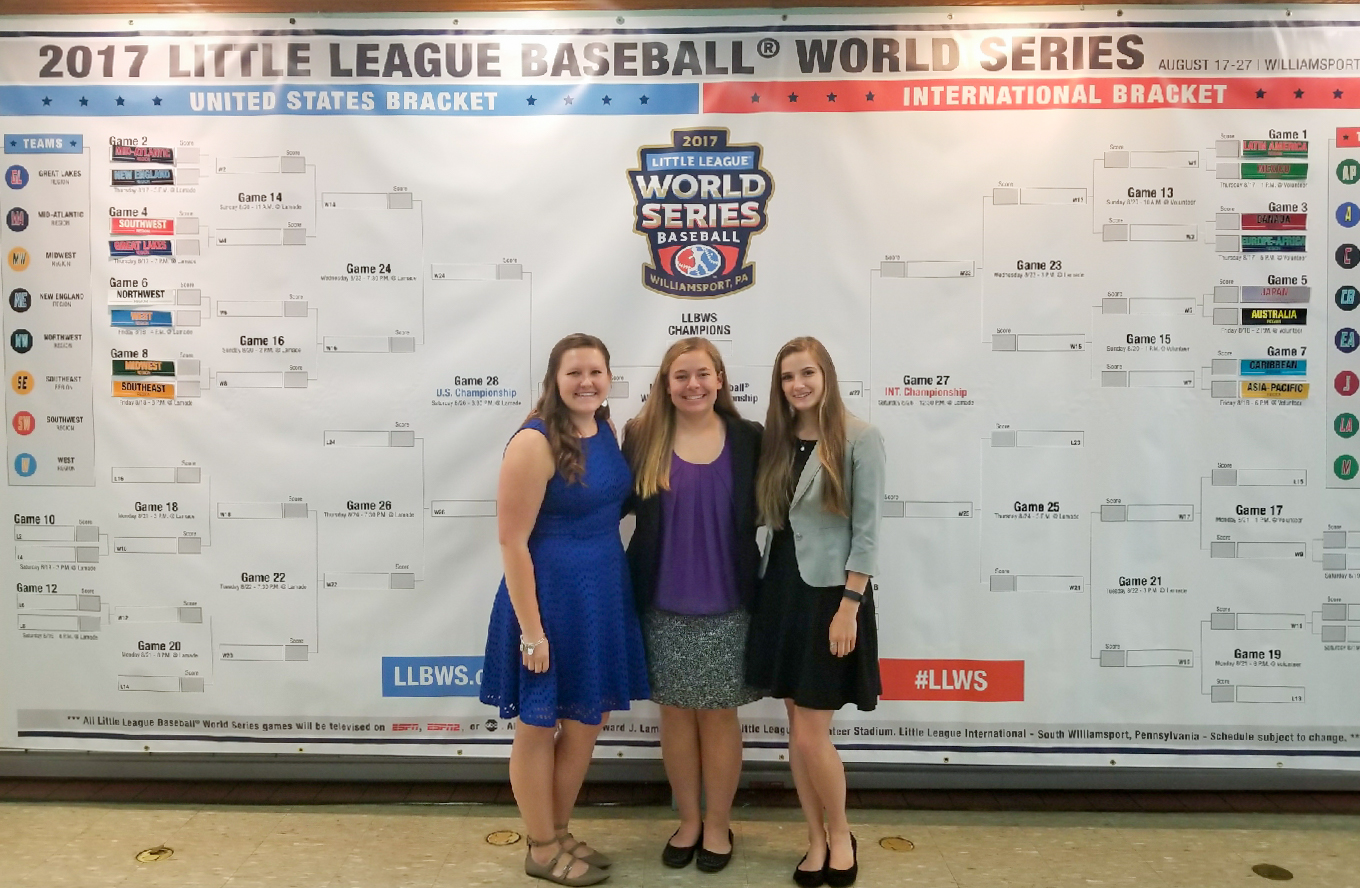 Ashely Weingartz, middle, stands with two other Little League World Series interns in front of the LLWS bracket during the Little League Luncheon.